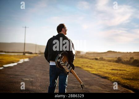 Man walking along a rural road with an electric guitar on his back. - Stock Photo