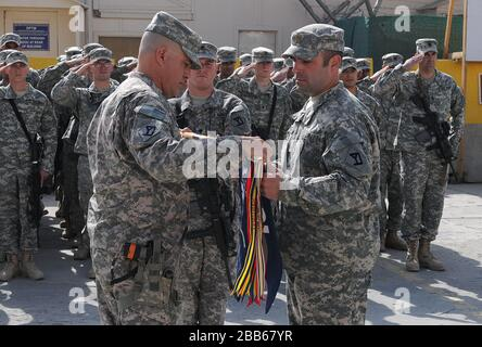 'English: Maj. Timothy Sawyer, right, commander of Headquarters and Headquarters Company (HHC), 1st Battalion, 181st Infantry Regiment, and 1st Sgt. David Parella, senior noncommissioned officer of HHC, uncase the guidon for the Massachusetts Army National Guard unit during a transition of authority ceremony Nov. 4, 2010, at Camp Phoenix in Kabul, Afghanistan. The 1-181st assumed the duties and responsibilities of the 1-178th Field Artillery Battalion, South Carolina Army National Guard, to provide force protection and security for a number of bases throughout the capital city of Kabul, as wel - Stock Photo