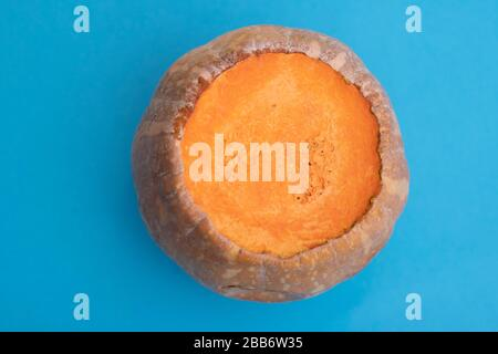 Big sliced pumpkin in center of blue paper, flat lay - Stock Photo