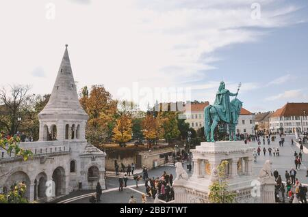 Budapest, Hungary - Nov 6, 2019: Tourists sightseeing and taking photos of Fishermans Bastion in the Hungarian capital city. Historical center, autumn trees. St. Stephen equestrian statue from behind. - Stock Photo