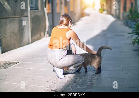 Young beautiful woman smiling happy and confident. Standing with smile on face caressing a cat at the town street - Stock Photo