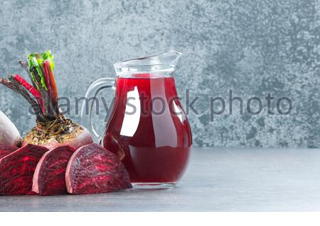 Fresh organic whole and sliced red beet, beetroot with glass bottle of beet water or juice on rustic table, healthy food beta vulgaris - Stock Photo