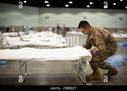 U.S. Air Force Tech. Sgt. Mario Lopez-Casas, a heating, ventilation, air conditioning and refrigeration specialist with the 146th Civil Engineer Squadron in the California Air National Guard's 146th Airlift Wing, puts sheets on a hospital bed while setting up a Federal Medical Station, March 29, 2020, inside the Los Angeles Convention Center as part of California's statewide COVID-19 response effort. This is the third medical station site the Airmen have set up in the state. (U.S. Air National Guard video by Staff Sgt. Crystal Housman) - Stock Photo