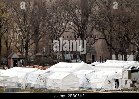 New York City, New York, United States. 30th Mar, 2020.Workers putting the finishing touches on an emergency hospital in New York City's Central Park to confront the coronavirus pandemic. The North Carolina based Christian organization Samaritan's Purse began constructing a 68-bed emergency field hospital across from Mount Sinai Hospital yesterday and it is expected to be operational on Tuesday, March 31st. The field hospital will be composed of a respiratory care unit with ICU capability. Credit: Adam Stoltman/Alamy Live News - Stock Photo