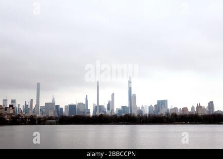 New York City, New York, United States. 30th Mar, 2020. Midtown Manhattan skyline as seen from the north end of Central Park Reservoir on Monday, on March 30th on a cloudy and damp day, and as New York's streets remained nearly empty in response to the coronavirus pandemic and shelter in place guidelines. Credit: Adam Stoltman/Alamy Live News - Stock Photo