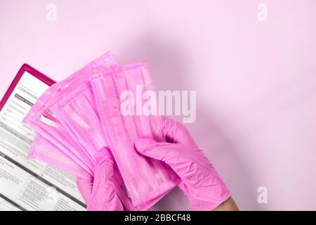 Protective facial masks deficit. Doctor or nurse holding in hands stack of facial masks over Coronavirus test form. Getting the COVID-19 test. Testing - Stock Photo