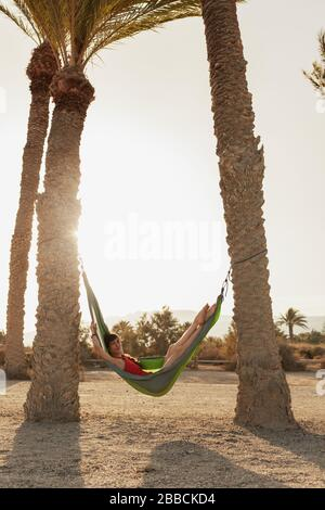 Young woman lying in his hammock among palm trees on the beach - Stock Photo