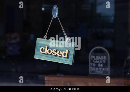 A sign on a restaurant saying 'Closed'. In the background you can see a notice saying 'Please wait to be seated'. Taken during the London Coronavirus - Stock Photo