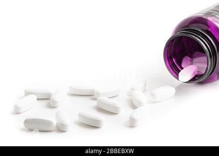 Medication bottle and white pills spilled on white background
