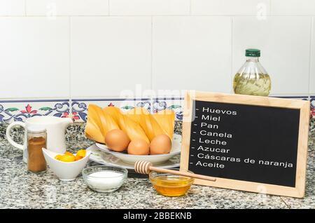Still life with the ingredients for making french toast. Blackboard say eggs, honey, bread, cinnamon, milk, sugar, orange peels, oil - Stock Photo