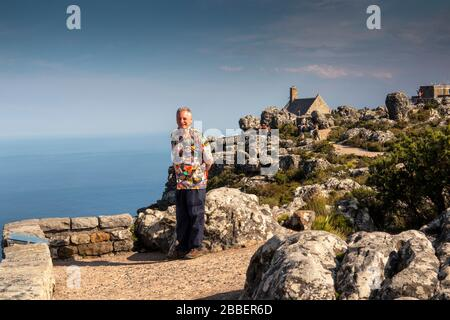 South Africa, Cape Town, Tafelberg Road, Table Mountain, senior tourist in colourful shirt on rocky path to Aerial Cableway station café and shop