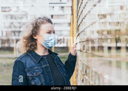 Eastern European concerned woman wearing medical mask outdoors, standing next to the mesh fence with residential building on background. Corona virus Stock Photo