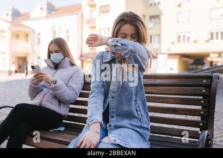 Girl in masks. Coronavirus theme. Women in the city sits on the bench without protective mask, during quarantine. Female sneeze and coughing - Stock Photo