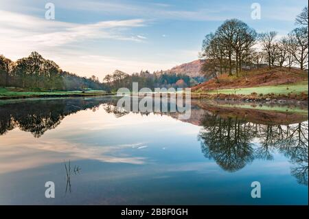 Tranquil woodland & fells landscape at Elter water a small lake / tarn near Elterwater in Great Langdale in the English Lake District, Cumbria - Stock Photo