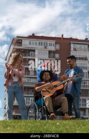 Latin American young man in a wheelchair playing the guitar next to some cheerful young people in a park with some buildings in the background - Stock Photo