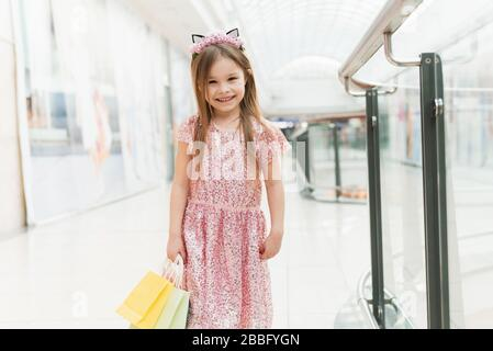 Portrait of a little happy girl in the mall. A smiling laughing girl in a pink dress with a cute rim with ears and with multi-colored bags in her hands is walking around the mall, looking at the camera.