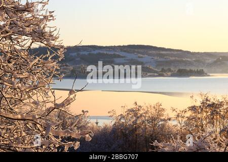 Panoramic view of scenic winter landscape with frozen lake Selbusjøen highlighted by golden sunlight, Selbustrand, Norway. - Stock Photo