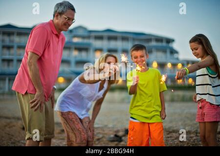Happy family having fun with sparklers on the beach at sunset - Stock Photo