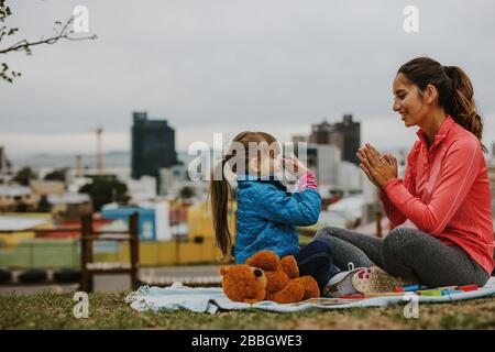 Side view of happy smiling woman and a girl child playing patty-cake game while sitting at a park. Little girl playing clapping game with her nanny ou - Stock Photo