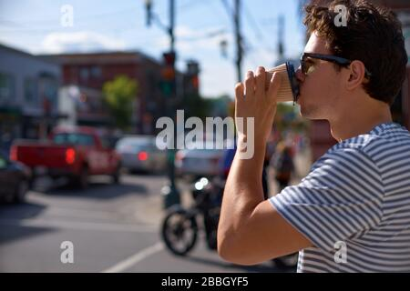 Enjoying city life. Handsome young man in having coffee to go while Magog city in background, Province of Quebec, travel on Canada - Stock Photo