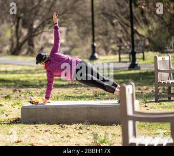 Berks County, Pennsylvania, USA-March 22, 2020: Fit young woman doing side planks  outdoors in public park. - Stock Photo