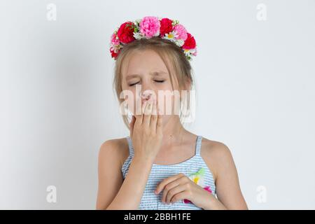 A sleepy grinning young girl, kid yawning. Closeup portrait of Caucasian kid model with floral headband and white blue striped dress with flowers isol - Stock Photo