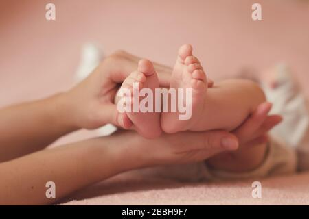 Mother holding baby feet in bed over pink background close up. Motherhood. Maternity. - Stock Photo