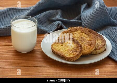 French toast - Przenice - slices of bread soaked in beaten eggs and milk and fried, with a glass of yogurt on a wooden table. Eggy bread, Bombay toast - Stock Photo