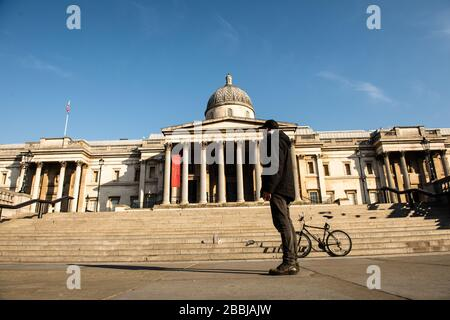 A lone man stands in Trafalgar Square, London, England.