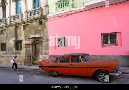 Pink wall with old red american fifties car, Centro, Havana, Cuba