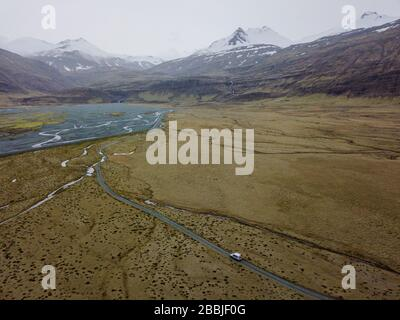 Aerial of car driving down gravel road in mountain valley in eas - Stock Photo