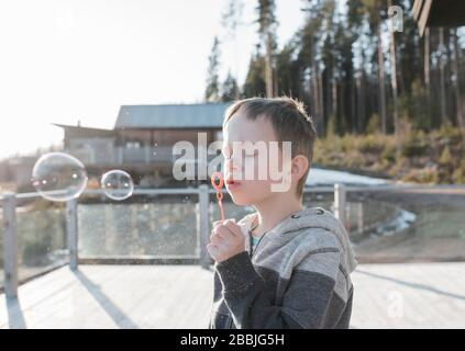 boy blowing bubbles on his balcony at home in Sweden - Stock Photo