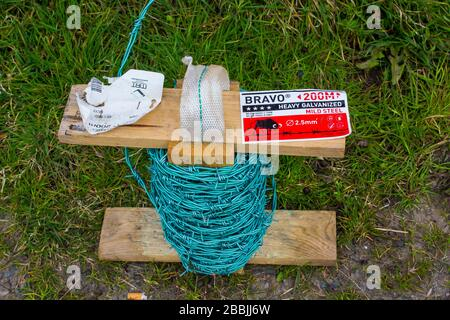 Barbed wire used as security perimeter fencing for the control of livestock in a farm setting. - Stock Photo