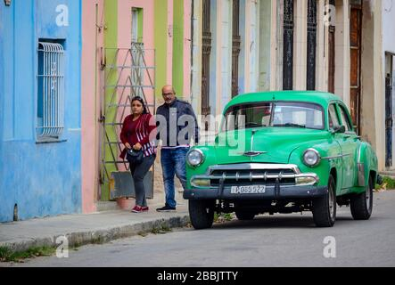 Old Chevrolet and passing couple, Havana, Cuba - Stock Photo