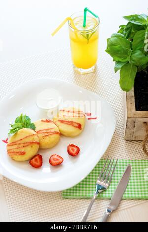 Cheese cookies with strawberry sauce, mint leaves on white plate and glass of lemon cold drink in restaurant. - Stock Photo