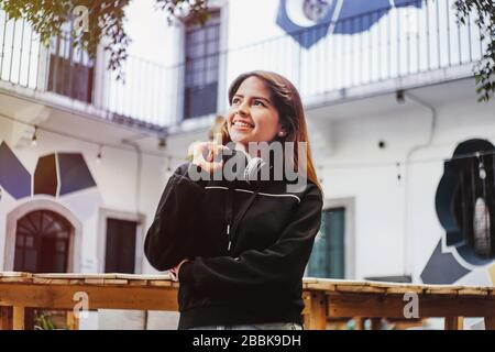 Happy latin teenager girl listening music in headphones in Mexico city