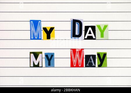 Phrase My Day My Way made from letters cutting from magazines on lined paper. Close-up.