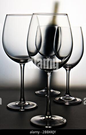 Close-up of wine glasses against red wine bottle - Stock Photo
