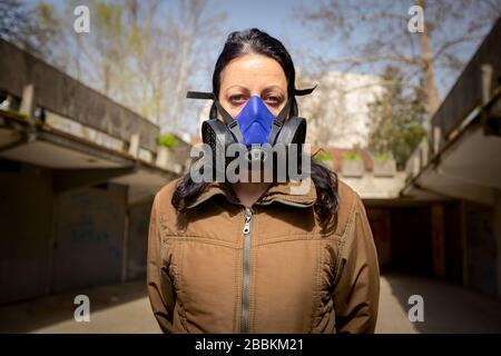 Woman is wearing industrial mask with paper filter her face for protection against virus COVID-19, Corona.