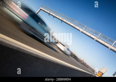 Car passing through a toll gate on a highway, highway charges, motion blurred image - Stock Photo