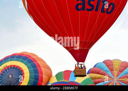 Red hot air balloon with basket and people rising above multi coloured balloons during the 34th Friese Ballonfeesten festival in Joure The Netherlands. - Stock Photo