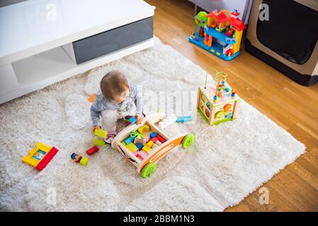 Portrait of one year old baby girl indoors in bright room
