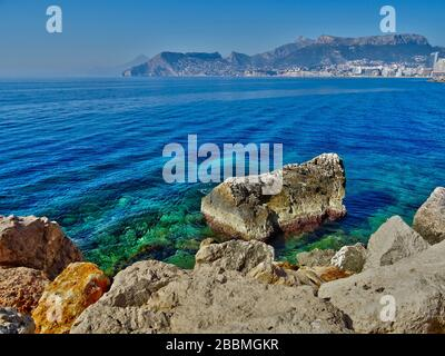 A view from Calpe on the Costa Blanca North in Spain. In the far distance, the vacation resort of Benidorm can be seen. - Stock Photo
