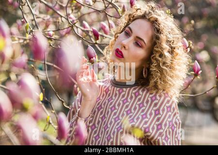 Portrait of blondy beautiful girl with curly long hair. Woman walks in the garden of blooming pink magnolia - Stock Photo