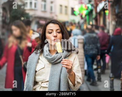 Beautiful young traveler woman in fashionable clothes enjoys eating piece of pineapple with a stick.Street food concept. Stock Photo