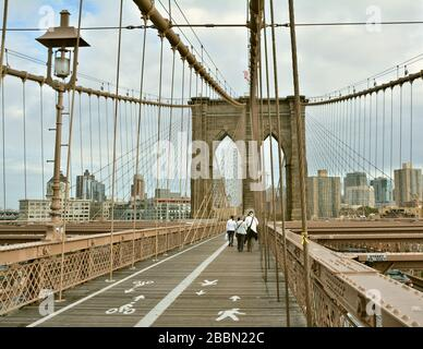NEW YORK CITY - OCTOBER 15, 2014: People walk on Brooklyn Bridge. Brooklyn Bridge connects boroughs of Manhattan and Brooklyn over East River - Stock Photo