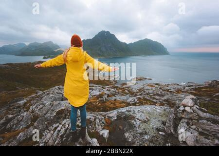 Woman traveler raised hands enjoying rainy mountains view traveling in Norway alone active vacations healthy lifestyle outdoor Lofoten islands landsca - Stock Photo
