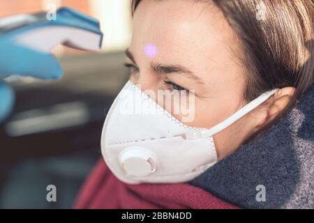 Temperature check point - the woman behind the wheel of the car in an anti-virus mask is subjected to temperature measurement. Coronavirus concept - r - Stock Photo
