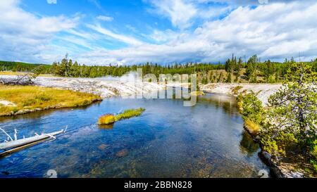 Hot water from the Oblong Geyser flowing into the Firehole River in the Upper Geyser Basin along the Continental Divide Trail in Yellowstone - Stock Photo