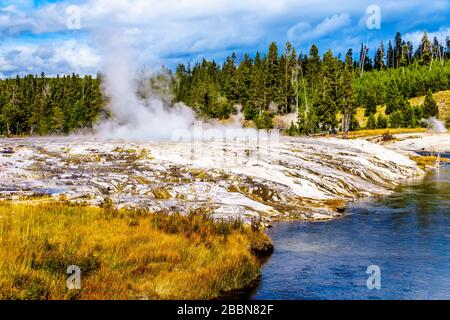 Hot water from the Oblong Geyser flowing into the Firehole River in the Upper Geyser Basin along the Continental Divide Trail in Yellowstone